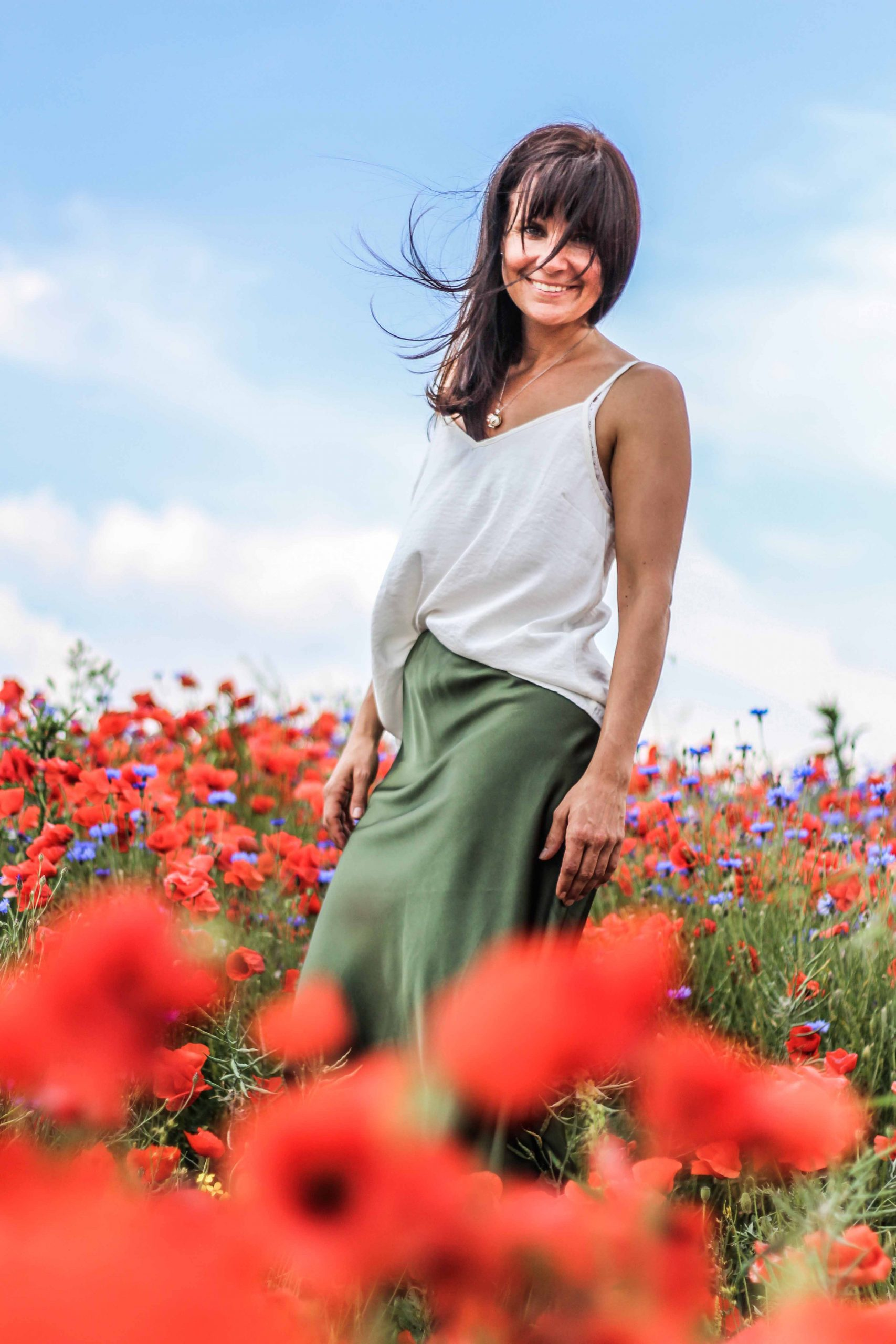 Andrea Conrad, deine Begleiterin, in einem roten Mohnfeld